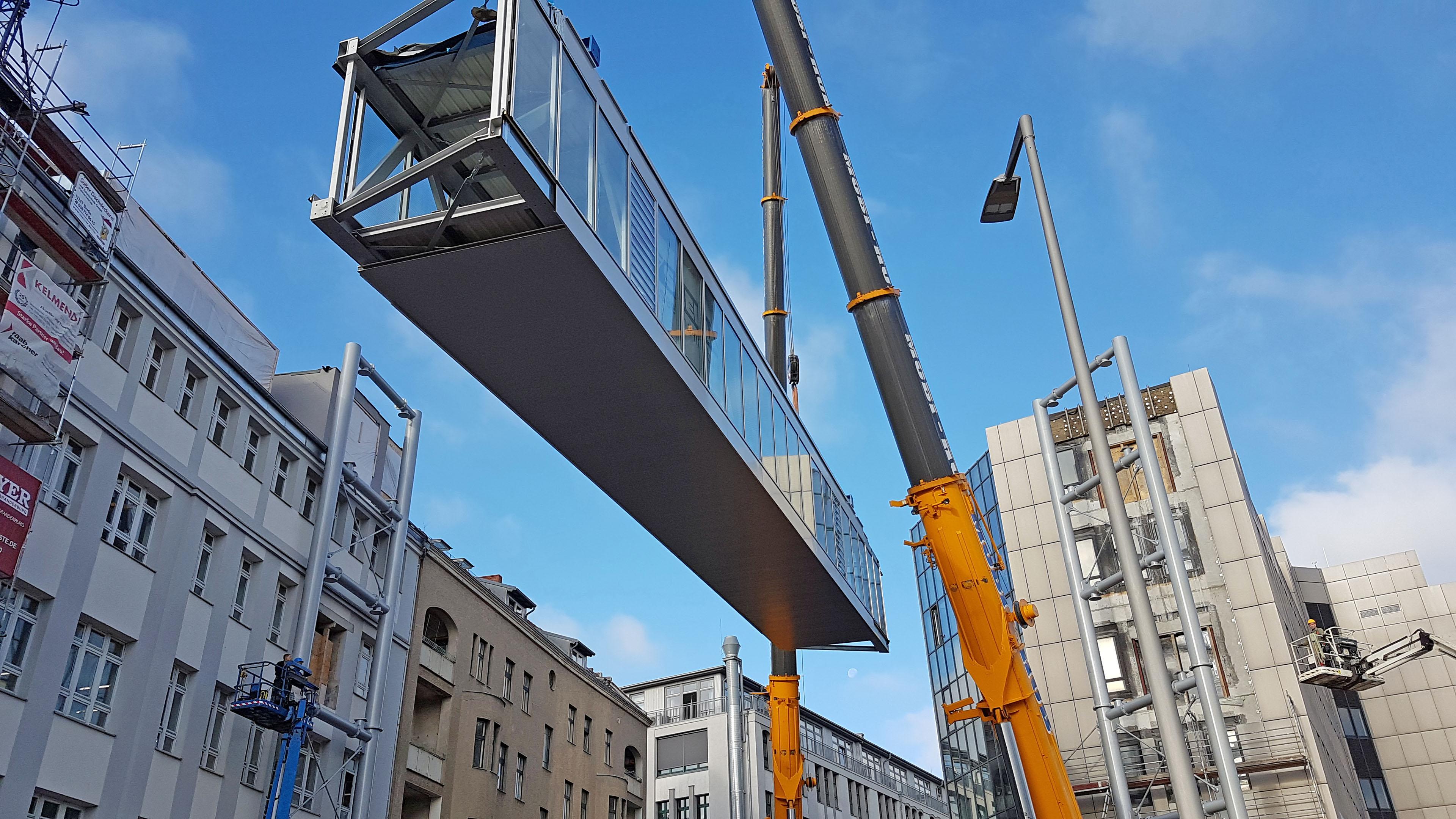 Einhub der ersten Verbindungsbrücke aus Stahl und Glas.