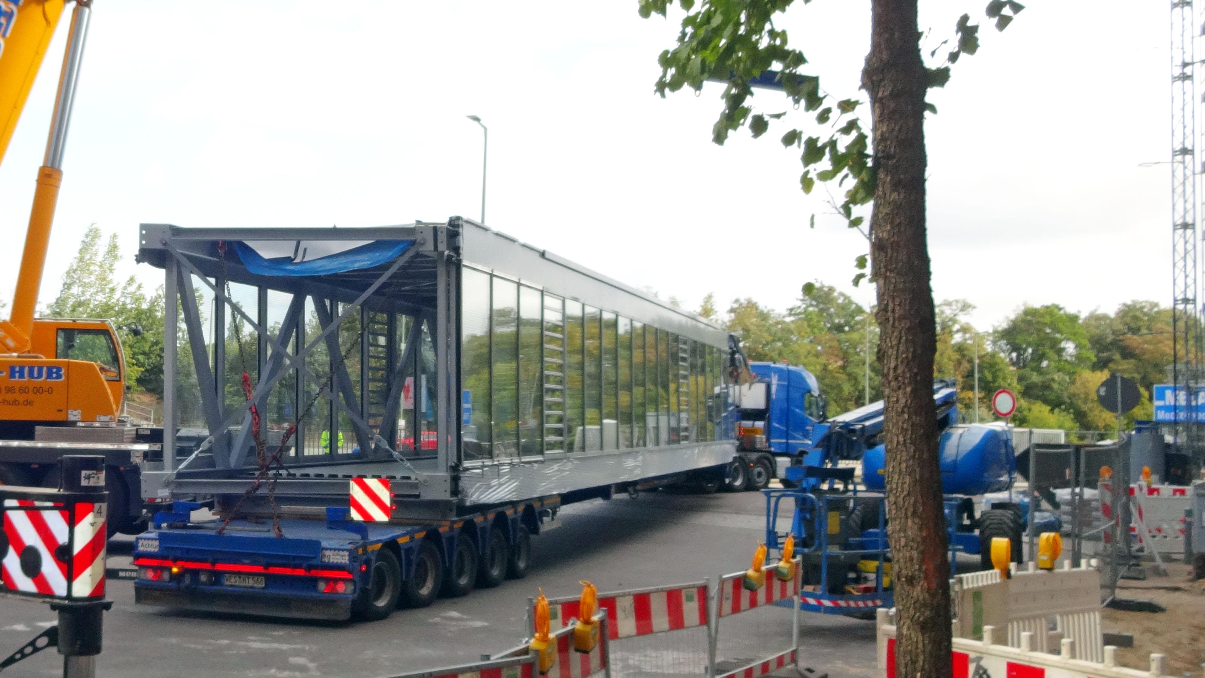 Transport einer vollverglasten Verbindungsbrücke aus Stahl und Glas