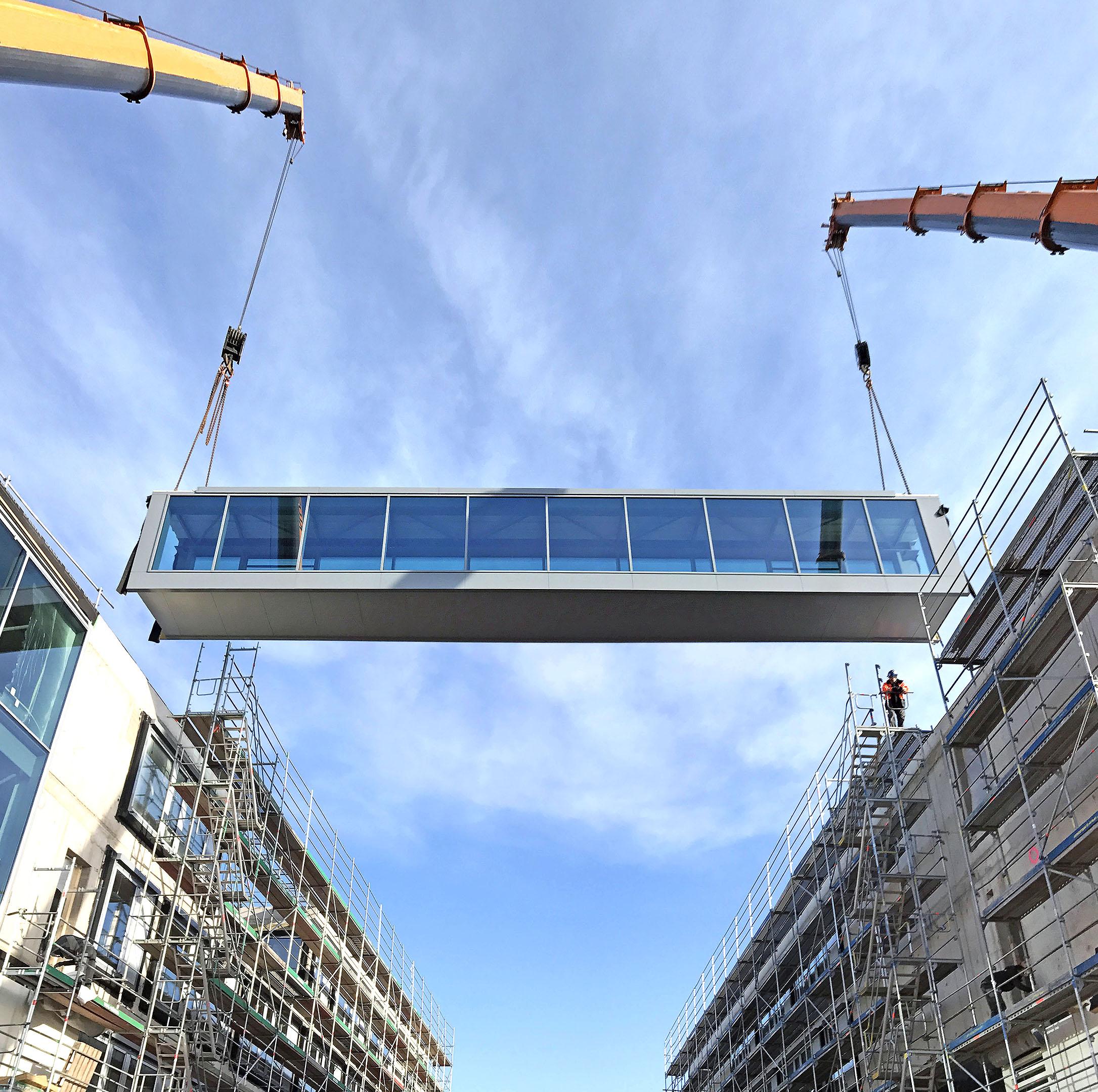 Einhub einer Verbindungsbrücke aus Stahl und Glas. Stahlbau und Metallbau.