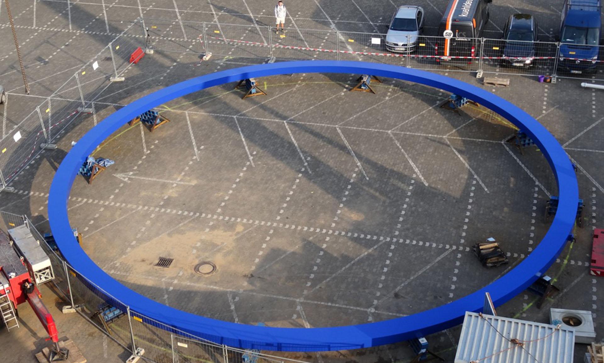 Blauer Stahlring Hochschule Darmstadt vor der Montage, am Boden vor einem Hochschulgebäude
